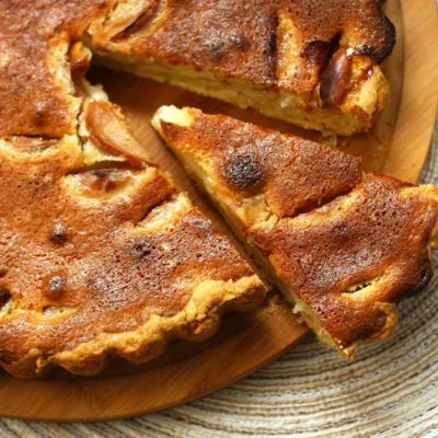 Apple pie with a browned crush, on a plate, with one piece cut.
