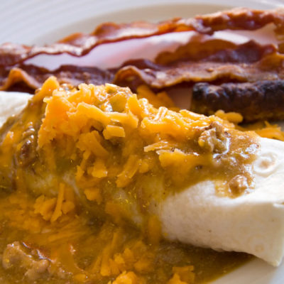 Breakfast burrito filled with sausage and egg, and topped with pork sausage gravy and cheese. Served with a side of bacon.