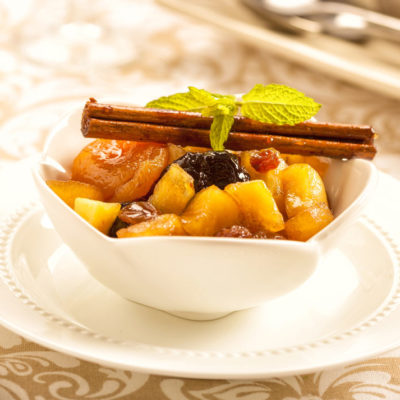 Hot Fruit Compote, a bowl of cooked fruit topped with a cinnamon stick