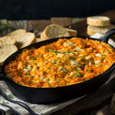 buffalo Chicken Dip in cast iron pan with bread