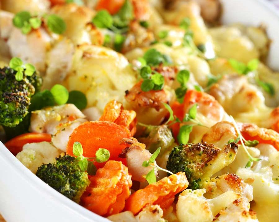 A medley of baked mixed vegetables such as carrots, broccoli and cauliflower with cheese