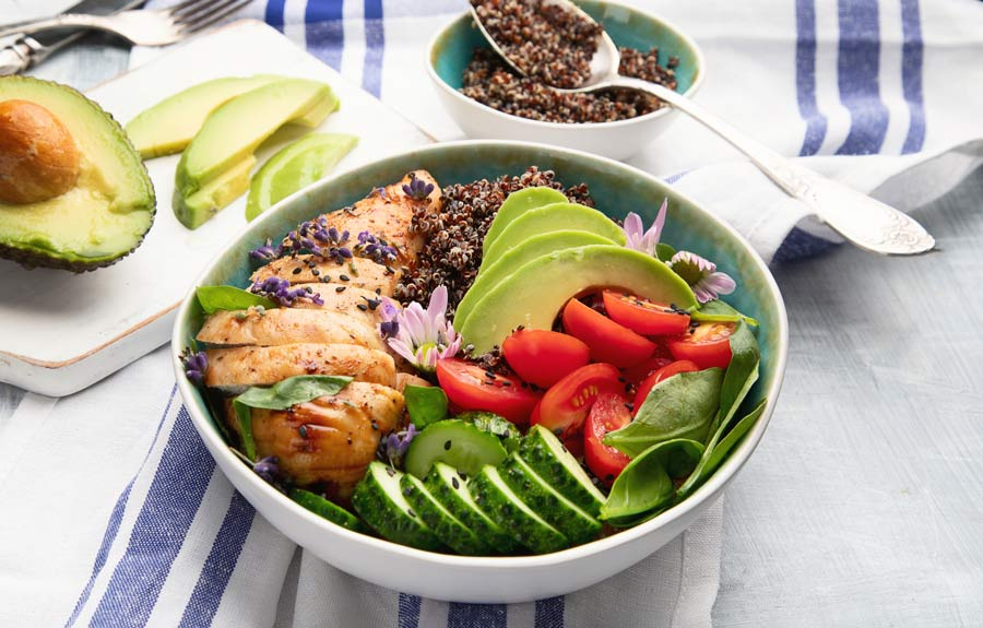 Quinoa bowl topped with chicken, avocado, tomatoes, and cucumbers