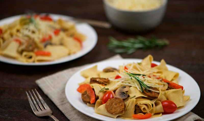 Sausage and Pappardelle Pasta on a white plate.