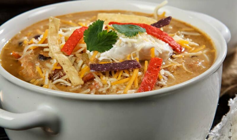 A bowl of chicken enchilada soup topped with cheese and tortilla strips.