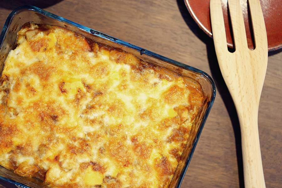 A glass baking dish willed with a cheesy casserole and a wooden spoon on the side.