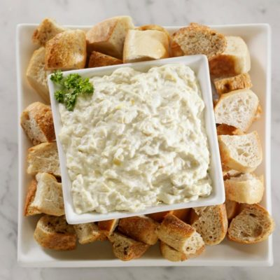 A platter with crackers and a bowl of artichoke dip.