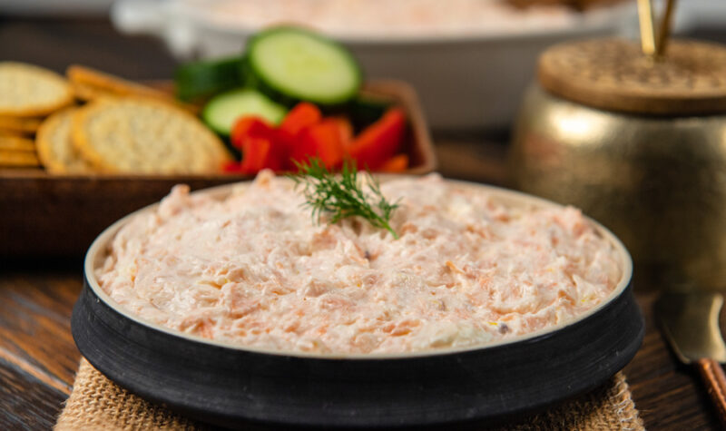 A bowl of salmon dip with a sprig of dill on top.