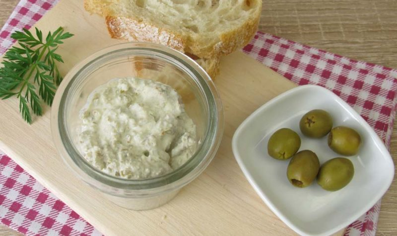 A glass bowl filled with cream cheese dip and a side of green olives and bread.