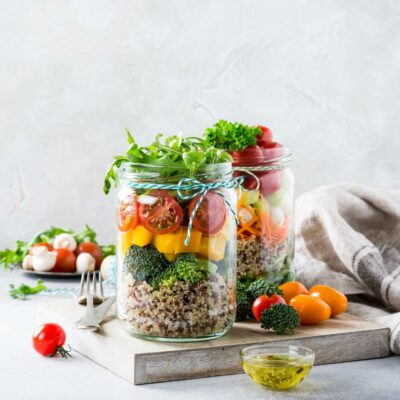 A mason jar filled with healthy salad ingredients.