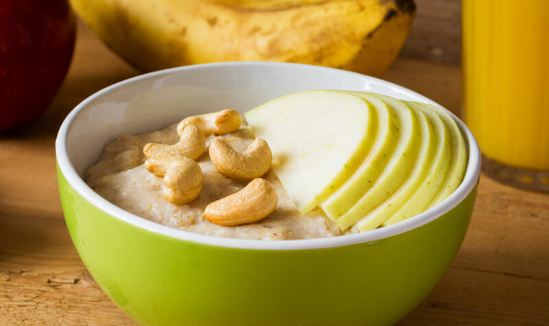 A bowl of oatmeal topped with cashews and apples
