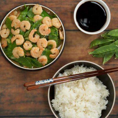 Shrimp stir fry with a side of rice and chopsticks