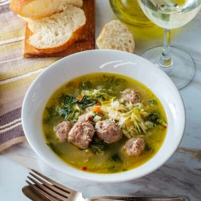 Italian wedding soup with meatballs in a white bowl.