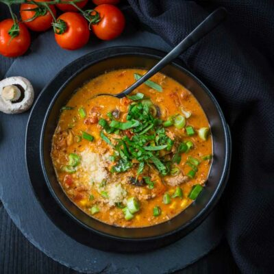 A black bowl filled with pizza soup with a spoon inside, and fresh mushrooms and tomatoes on the side.