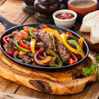 A cast iron skillet with steak fajitas and peppers.