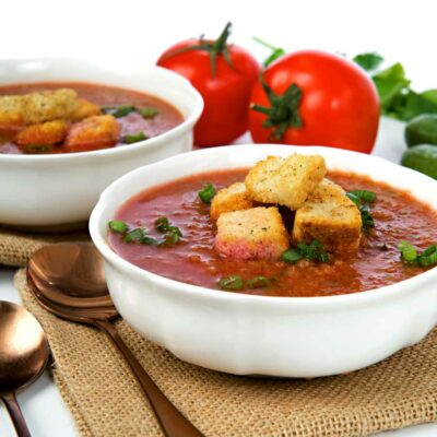 2 bowls of gazpacho with croutons on top.