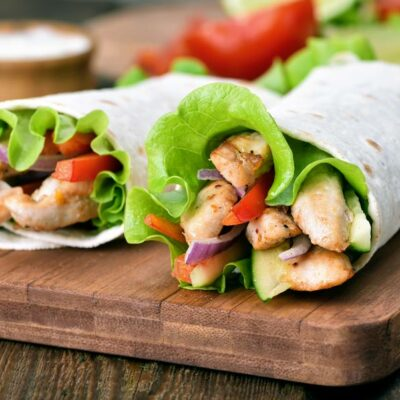 A tortilla filled with chicken fajita meat and lettuce and tomato