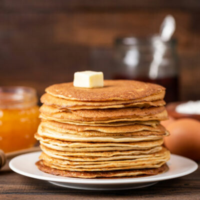 Buckwheat pancakes on a white plate with honey in the background