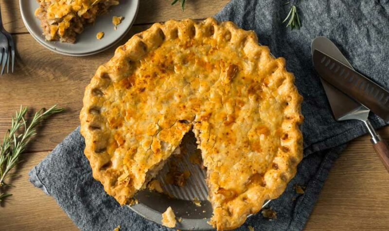 Canadian meat pie with a piece taken out.