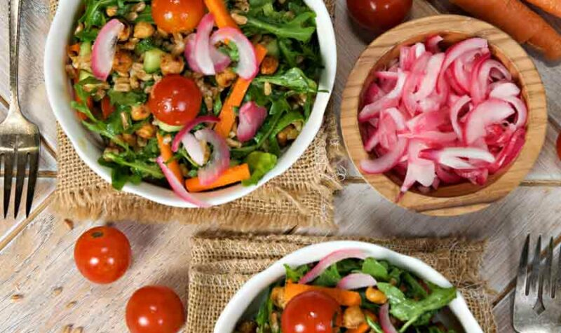 2 white bowls with farro salad, and pickled onions, carrots and cherry tomatoes on the side.