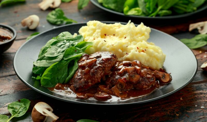 Cube steak on a plate with gravy, mashed potatoes and greens.