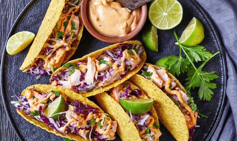 Fish tacos on a plate with crema and lime on the side