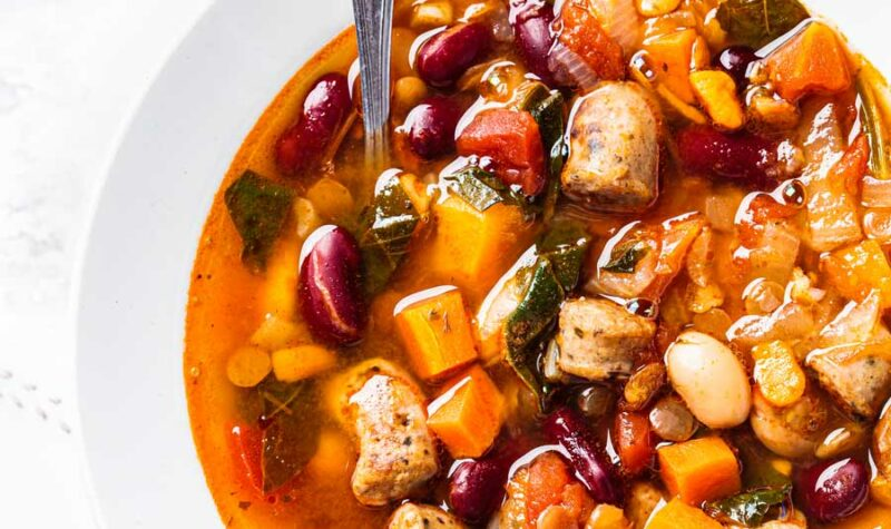 Sweet Potato Minestrone soup in a white bowl with a spoon.