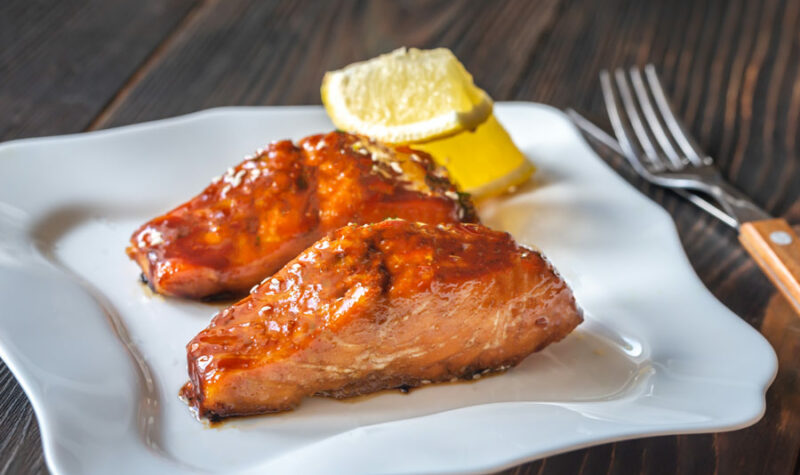 Marinated salmon on a plate with fresh lemon wedges in the background