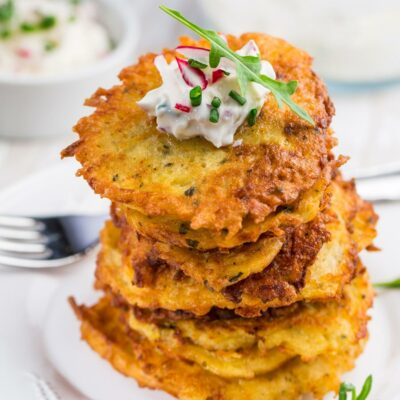 Potato pancakes stacked on a plate and topped with sour cream