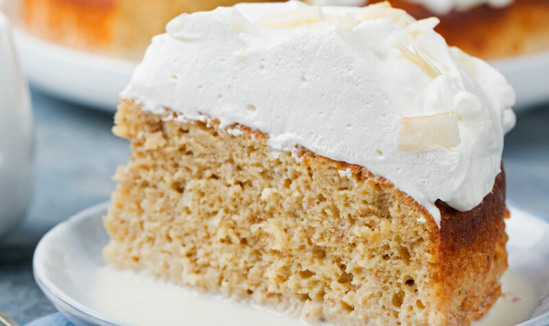 A piece of Tres Leches cake on a white plate.